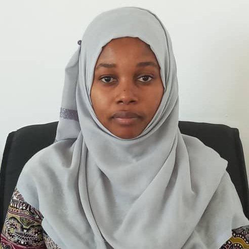 A Tanzanian woman wearing a light grey jihab.