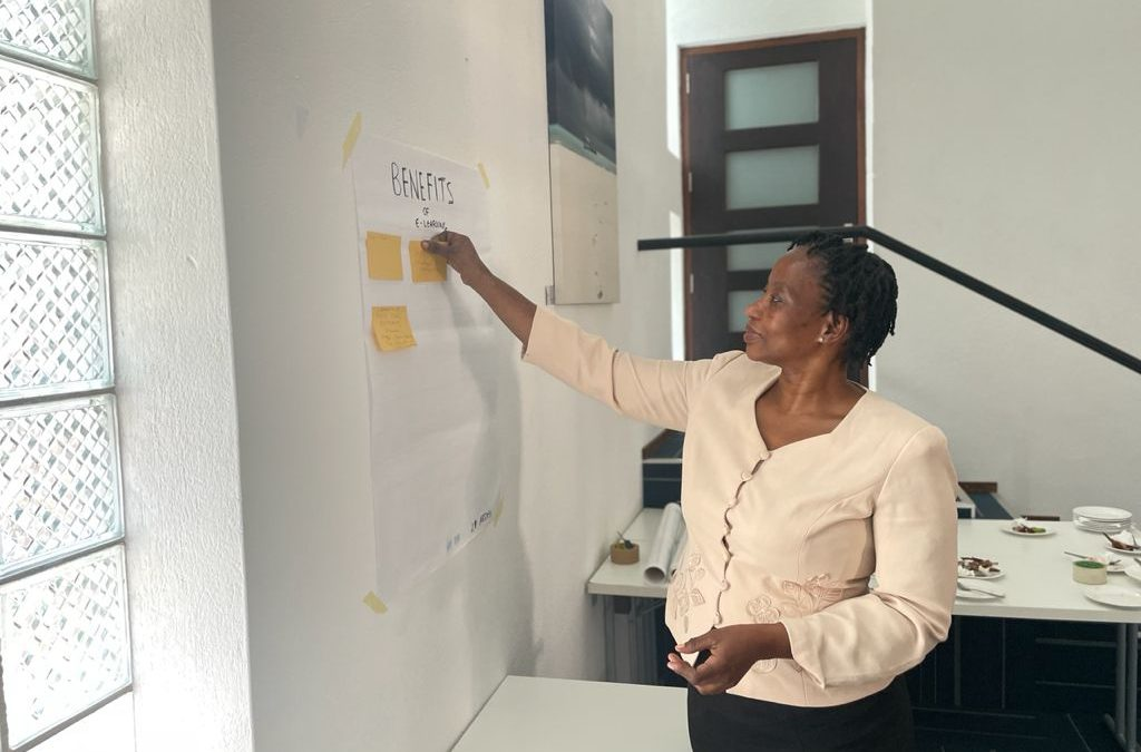 Woman placing post-it notes in the wall of the benefits and challenges of e-learning